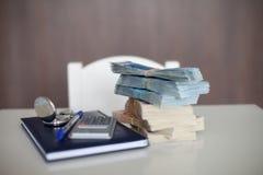 Taschenrechner mit dem Tagebuch, den Eurorechnungen und dem Stift, liegend auf einer Tabelle Stockfotos
