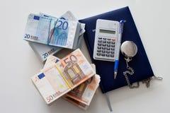 Taschenrechner mit dem Tagebuch, den Eurorechnungen und dem Stift, liegend auf einer Tabelle Lizenzfreies Stockbild