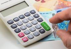 Taschenrechner mit Euroanmerkungen über Hintergrund Grüner Schlüssel mit Wort Bargeld Stockfoto
