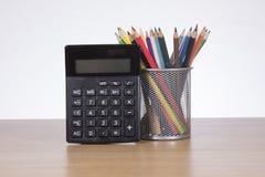 Taschenrechner mit farbigen Bleistiften im Behälter Lizenzfreie Stockbilder