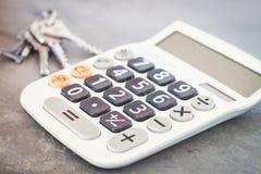Taschenrechner mit Schlüsseln auf grauem Hintergrund Lizenzfreies Stockfoto