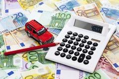 Taschenrechner mit Stift- und Spielzeugauto auf Haufen von Euroanmerkungen Stockfotografie