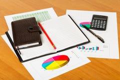 Taschenrechner, Notizblock, Stift und Bleistift auf Hintergrund des Desktops Lizenzfreies Stockfoto