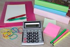 Taschenrechner, Notizbuch, Markierungen und Büroartikel, Geschäftszubehör auf Tabelle Lizenzfreie Stockbilder