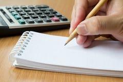 Taschenrechner, Notizbuch und Bleistift in der Hand für berechnen Lizenzfreie Stockfotos