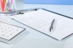 Taschenrechner, Stift und Dokumente auf einem Schreibtisch stockbild