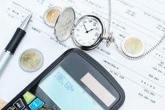 Taschenrechner, Taschenuhren, Geld. Stockbild