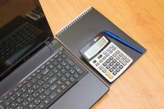 Taschenrechner u. Laptop und Notizbuch auf dem Tisch Lizenzfreie Stockfotos