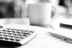 Taschenrechner u. Stift über Papier auf dem Tisch mit UnschärfeKaffeetassehintergrund Stockfotos