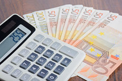 Taschenrechner und Banknoten auf dem Tisch Lizenzfreies Stockfoto