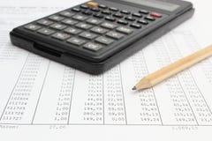 Taschenrechner und Bleistift, die auf Tabelle liegen Stockbild