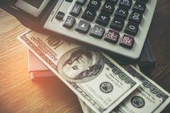 Taschenrechner und 100 Dollarschein auf hölzernem Schreibtisch Lizenzfreie Stockfotografie