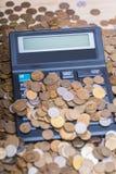 Taschenrechner und ein Stapel Münzen Stockbild