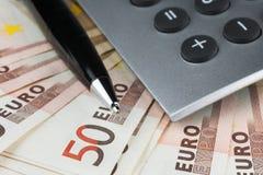 Taschenrechner und ein Stift, der auf dem Euro liegt Lizenzfreies Stockbild