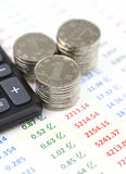 Taschenrechner und Münzen auf Buchführungsangabeliste Stockfotos