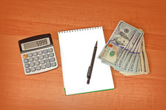 Taschenrechner und Notizblock, die auf Banknoten auf hölzernem Schreibtisch liegen Lizenzfreie Stockbilder