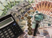Taschenrechner und Vergrößerungsglas auf dem Hintergrund des Geldes Stockfotografie