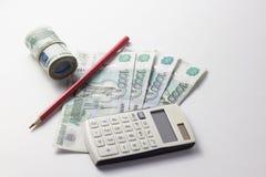 Taschenrechner und viel Geld auf einem weißen Hintergrund Lizenzfreies Stockfoto