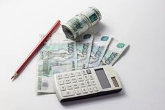 Taschenrechner und viel Geld auf einem weißen Hintergrund Lizenzfreie Stockfotografie