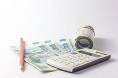 Taschenrechner und viel Geld auf einem weißen Hintergrund Stockfotografie