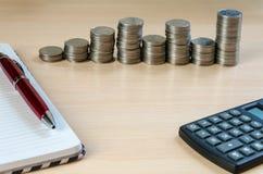 Taschenrechnernotizblockstift und -münzen Stockfoto