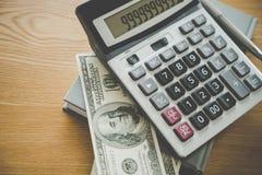 Taschenrechnernotizbuch und 100 Dollarschein auf Schreibtisch Lizenzfreie Stockfotos