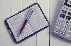 Taschenrechnernotizbuchstift auf Holztisch lizenzfreie stockfotos