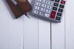 Taschenrechnernotizbuchstift auf Holztisch stockfotos