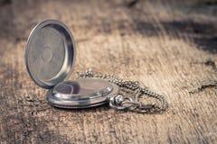 Taschenuhr am alten hölzernen Hintergrund Stockfotos