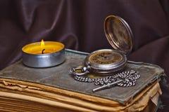 Taschenuhr, antike Bücher, Kerze Lizenzfreie Stockbilder