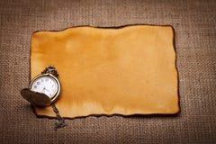 Taschenuhr auf altem Papier Stockbild