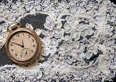 Taschenuhr auf weißer Spitze Stockbild