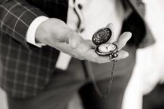 Taschenuhr in der Hand eines Mannes lizenzfreie stockbilder