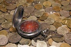 Taschenuhr gegen russische Münzen Stockbilder