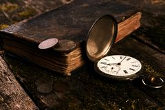 Taschenuhr mit einem alten antiken Bibelbuch und einem alten Kupfer c Stockfotos