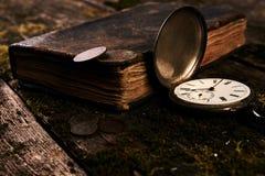 Taschenuhr mit einem alten antiken Bibelbuch und einem alten Kupfer c Lizenzfreie Stockfotografie