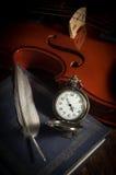 Taschenuhr mit Feder auf Buch und Violine Stockfotografie
