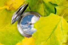 Taschenuhr und Herbstblätter Stockbilder