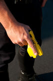 Taser weapon. A police officer holding a Taser stun gun in his hand ready to use Royalty Free Stock Photos