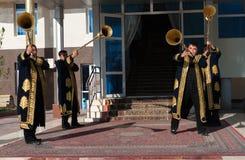 TASHKENT UZBEKISTÁN - 9 de diciembre de 2011: Hombres del músico en los kaftans tradicionales que juegan el karnay Imágenes de archivo libres de regalías