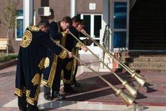 TASHKENT UZBEKISTÁN - 9 de diciembre de 2011: Hombres del músico en los kaftans tradicionales que juegan el karnay fotos de archivo libres de regalías