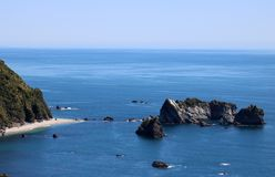 Tasman Sea from Knights Point Lookout, Haast, NZ. Beach with seals under a cliff and rocks off the West Coast of South Island, New Zealand  seen from Knights Stock Image