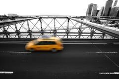 Tassì che scorre veloce sul ponte di Brooklyn di New York Fotografia Stock Libera da Diritti