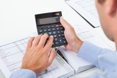 Tassa calcolatrice dell'uomo d'affari in ufficio Fotografie Stock Libere da Diritti