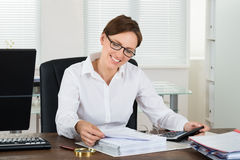 Tassa calcolatrice della donna di affari allo scrittorio immagine stock