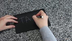 TASSA femminile di ortografia della mano sulla tavola situantesi di carta nera stock footage
