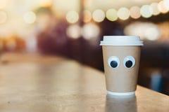 Tasse à emporter de café avec des yeux de bande dessinée en café Concept de café hospitalier images libres de droits
