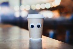 Tasse à emporter de café avec des yeux de bande dessinée en café Concept de café hospitalier photos stock