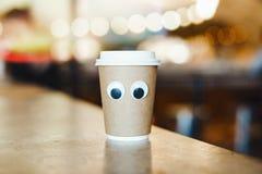 Tasse à emporter de café avec des yeux de bande dessinée en café Concept de café hospitalier photos libres de droits