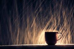 Tasse éclairée à contre-jour de café chaud sur le fond neigeux de nuit ; Photographie stock